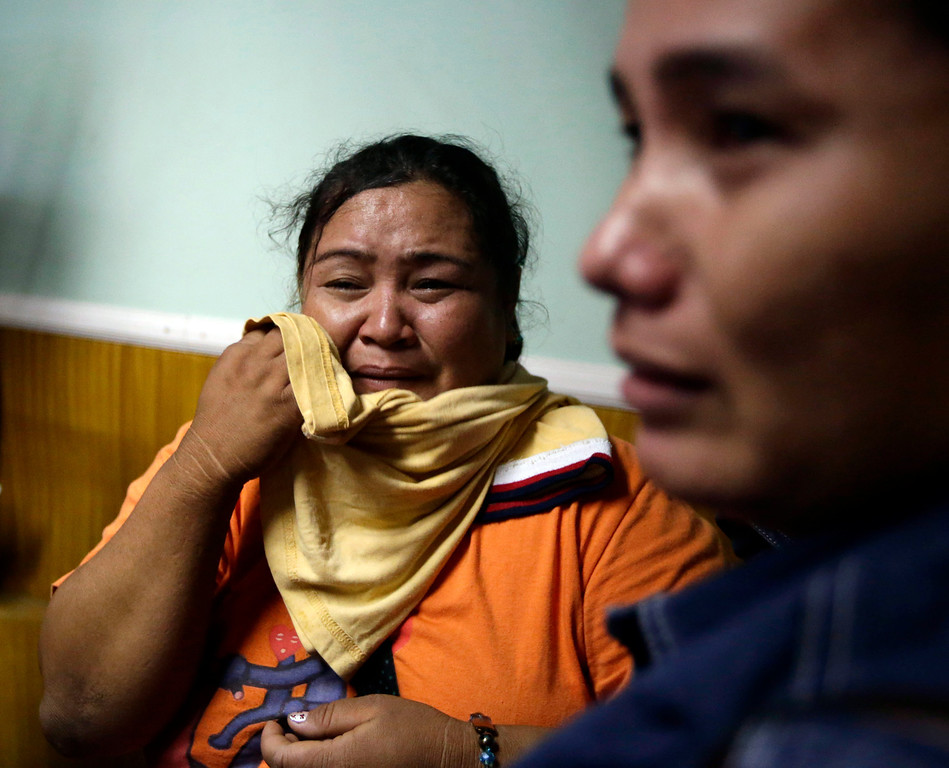 . A survivor, left, of the ill-fated passenger ferry MV Thomas Aquinas, cries as she is reunited with her relatives at the ticketing office of a shipping company, Saturday Aug. 17, 2013, a day after the ferry collided with a cargo ship, the MV Sulpicio Express Siete, off the waters of Talisay city, Cebu province in central Philippines. Divers combed through the sunken ferry Saturday in search of dozens of people missing after the collision that sent passengers jumping into the ocean and leaving many others trapped. At least 31 were confirmed dead and hundreds rescued. (AP Photo/Bullit Marquez)
