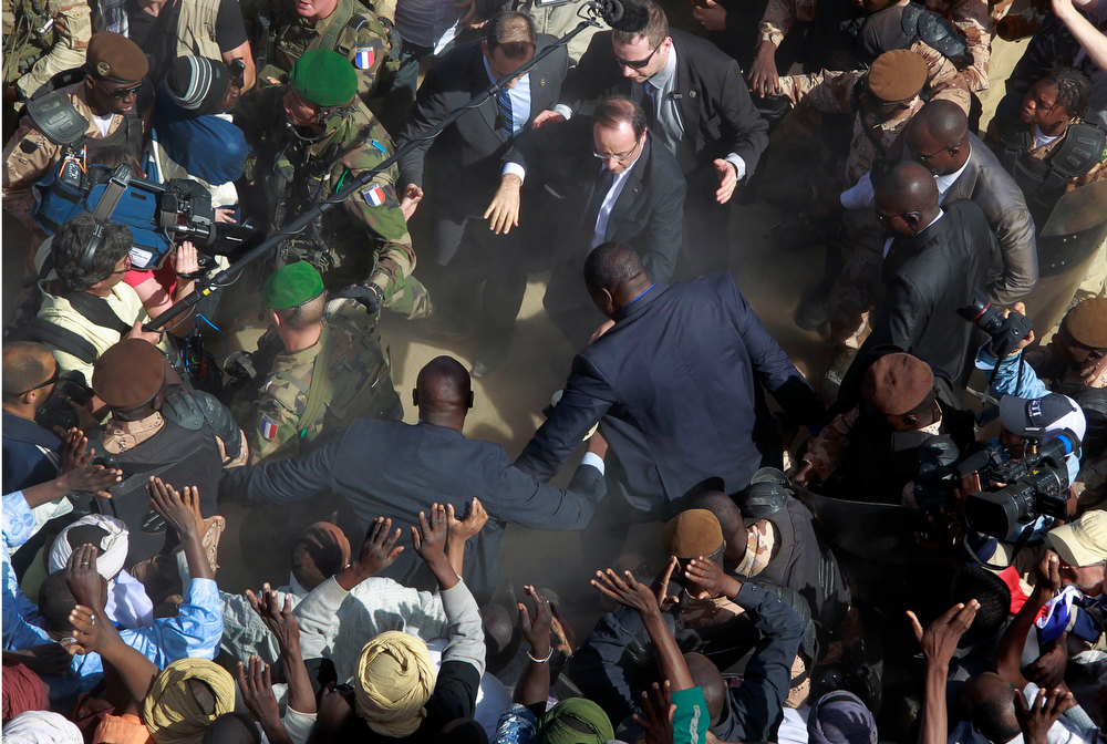 Description of . French President Francois Hollande is surrounded by security as he greets well-wishers during his two-hour-long visit to Timbuktu, Mali, Saturday Feb. 2, 2013.(AP Photo/Jerome Delay)