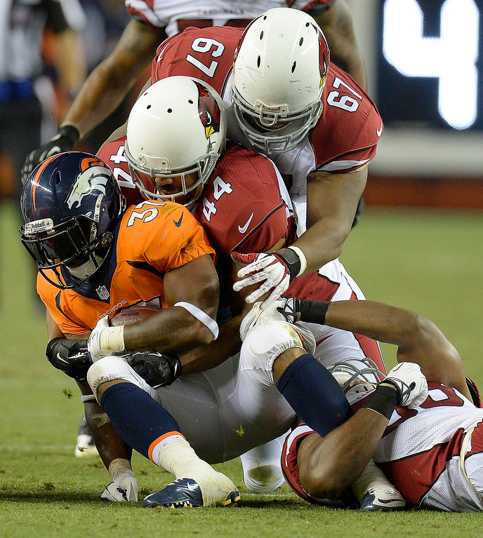 . Denver Broncos running back Jeremiah Johnson (37) gets gang tackled by Arizona Cardinals nose tackle Padric Scott (67), inside linebacker Daryl Washington (58) and linebacker Kenny Rowe (44) during the first half on August 29, 2013 at Sports Authority Field at Mile High. The Denver Broncos hosted the Arizona Cardinals in the final game of the preseason. (Photo by John Leyba/The Denver Post)