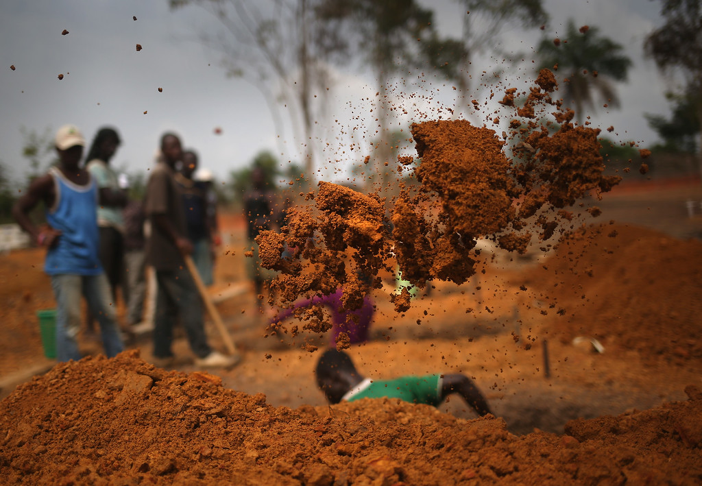 ". A grave digger works in the U.S.-built  cemetery for ""safe burials\"" on January 27, 2015 in Disco Hill, Liberia.  (Photo by John Moore/Getty Images)"