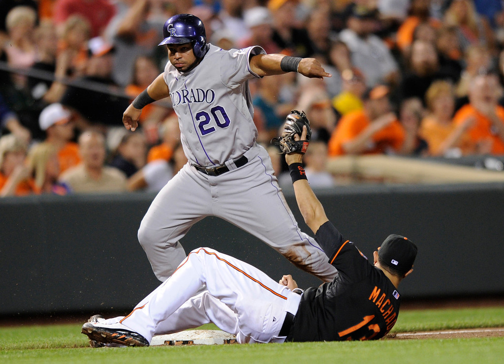 . Colorado Rockies\' Wilin Rosario (20) is safe at third on a wild pitch against the Baltimore Orioles third baseman Manny Machado (13) during the fifth inning of a baseball game, Friday, Aug. 16, 2013, in Baltimore. (AP Photo/Nick Wass)