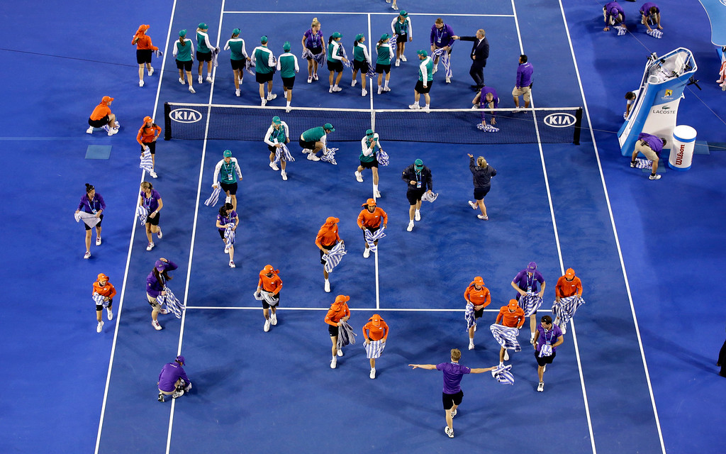 . Ground staff dry the court surface of Rod Laver Arena in the rain delay during the women\'s singles final between Serena Williams of the U.S. and Maria Sharapova of Russia at the Australian Open tennis championship in Melbourne, Australia, Saturday, Jan. 31, 2015.  (AP Photo/Lee Jin-man)