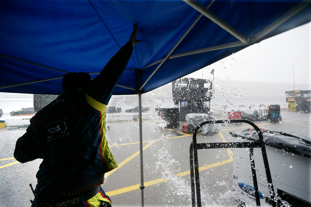 . A crew member for Brett Moffitt moves rain off the tent during a rain delay at the NASCAR Sprint Cup series auto race at Michigan International Speedway, Sunday, June 14, 2015, in Brooklyn, Mich. (AP Photo/Carlos Osorio)