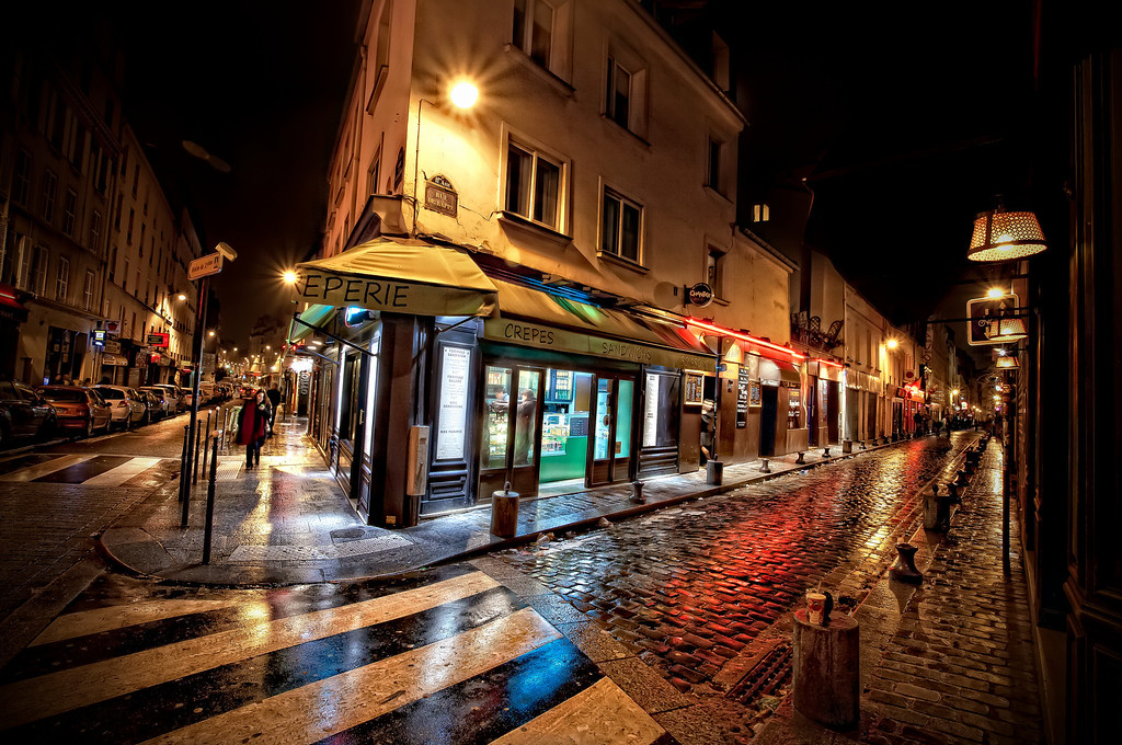 <h2>Creperie on the Rue de Roquette</h2> The black and white stripes of the crosswalk reminded me of the cover of the Beatles' Abby Road album. Remember that? Then there was the cobblestones reflecting the lights, the lady on her cell phone, the folks inside getting their crepes.  Just one of those moments in time that's here for a second... and then gone.  But now... here.  You get my drift.