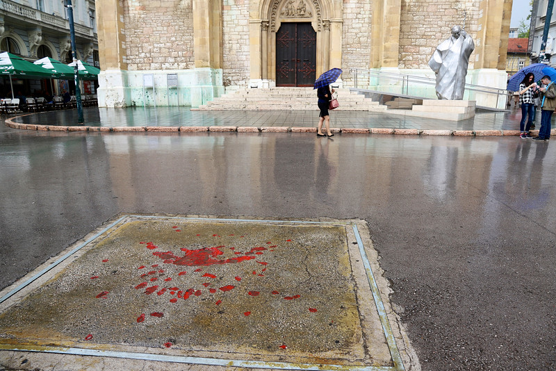 This is called a Sarajevo Rose - Mortar rounds landing on concrete created these unique scars in the pavement that were filled in with red resin. - in front of the Catholic Cathedral, Sarajevo