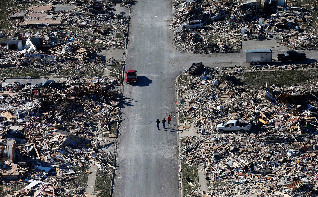 . This aerial view on Monday, Nov. 18, 2013, shows people walking down a street where homes once stood that were  destroyed by a tornado that hit the western Illinois town of Washington. It was one of the worst-hit areas after intense storms and tornadoes swept through Illinois. The National Weather Service says the tornado that hit Washington had a preliminary rating of EF-4, meaning wind speeds of 170 mph to 190 mph. (AP Photo/Charles Rex Arbogast)