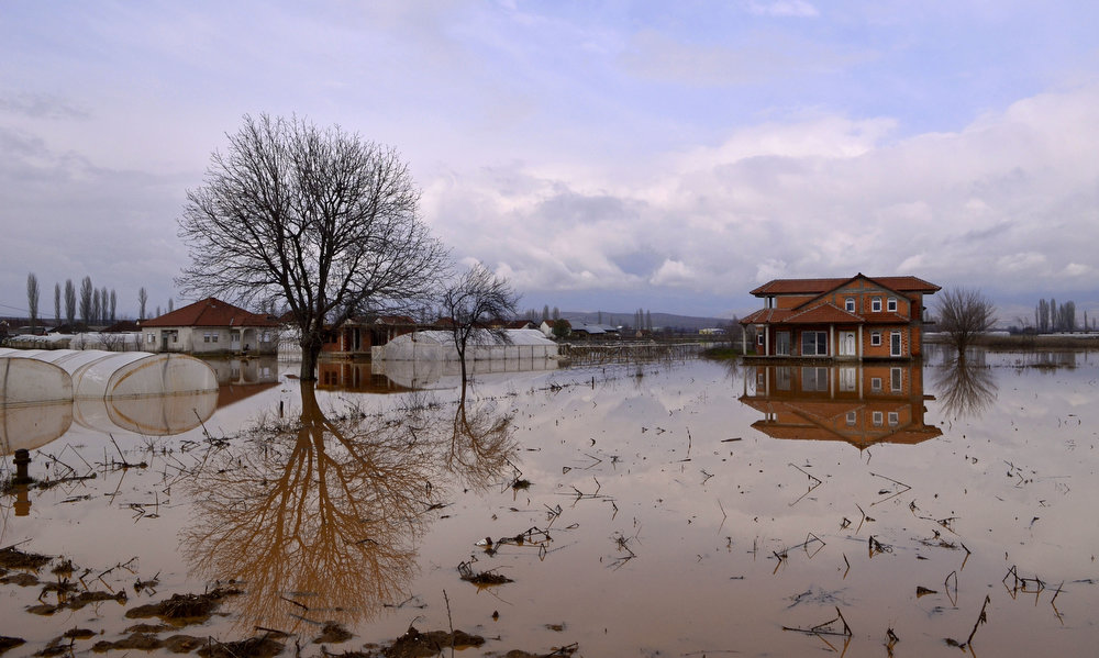 Description of . A flooded house and polytunnels cast their reflection in the water in the village of Gradosorci, southeastern Macedonia, Wednesday, Feb. 27, 2013. About 1,000 people had been evacuated due to the floods in eastern Macedonia, after three days of heavy rain. (AP Photo/Boris Grdanoski)