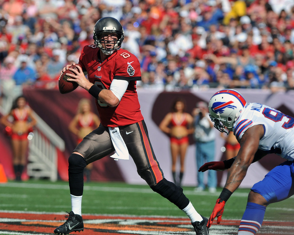 . Quarterback Mike Glennon #8 of the Tampa Bay Buccaneers rolls out and tosses a 38-yard touchdown pass in the 1st quarter against the Buffalo Bills  December 8, 2013 at Raymond James Stadium in Tampa, Florida.  (Photo by Al Messerschmidt/Getty Images)