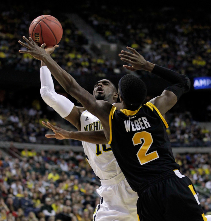 . Michigan Wolverines Tim Hardaway Jr. shoots while defended by VCU Rams Briante Weber during the second half of their third round NCAA tournament basketball game in Auburn Hills, Michigan March 23, 2013. REUTERS/Jeff Kowalsky