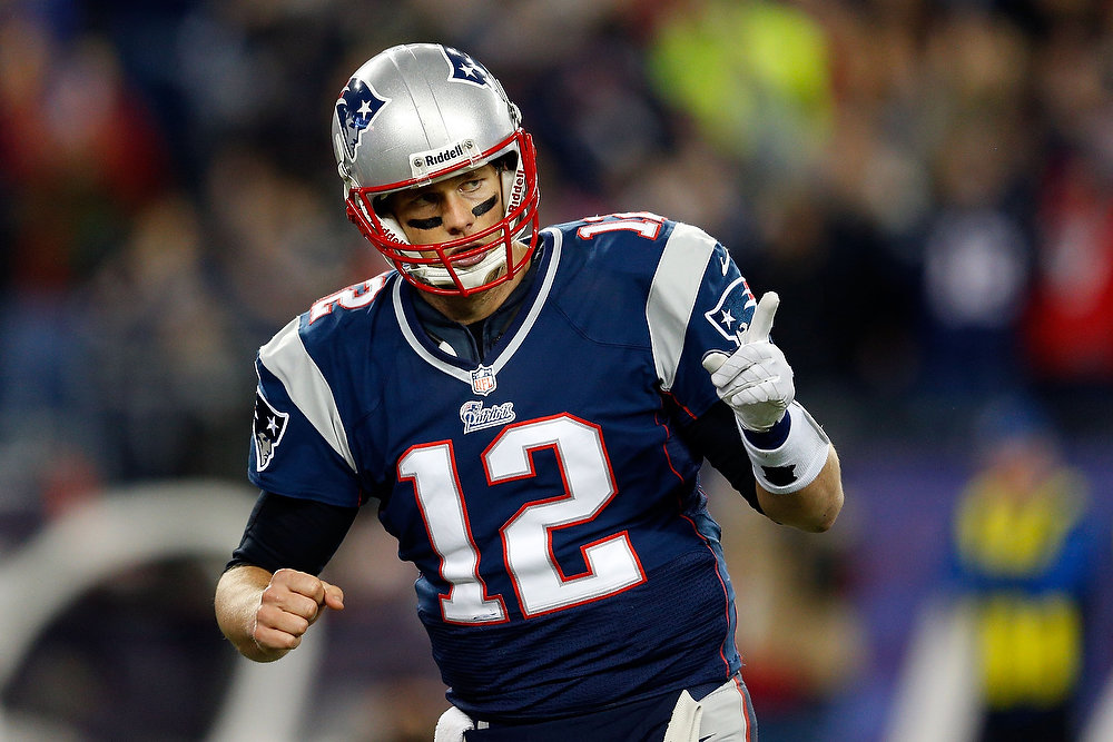 Description of . Tom Brady #12 of the New England Patriots reacts after a touchdown in the second quarter against the Houston Texans during the 2013 AFC Divisional Playoffs game at Gillette Stadium on January 13, 2013 in Foxboro, Massachusetts.  (Photo by Jim Rogash/Getty Images)