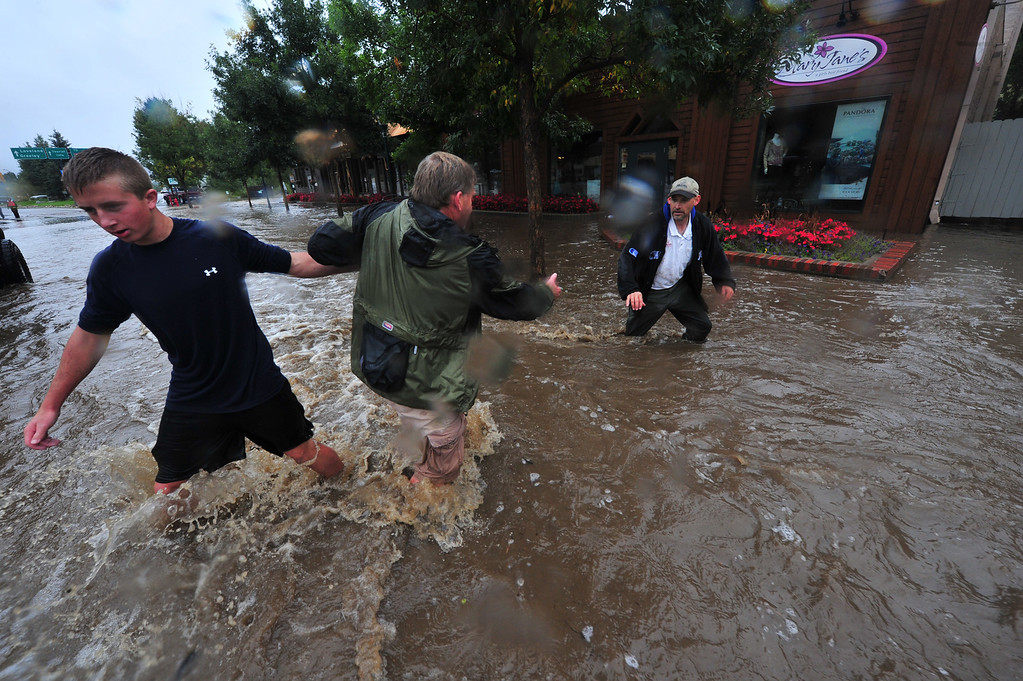 . Volunteers help each other across fast-moving water on Elkhorn Ave. on Thursday evening, September 12, 2013. Residents got together to help sandbag businesses downtown and keep each other as safe as possible. Walt Hester/Estes Park Trail-Gazette