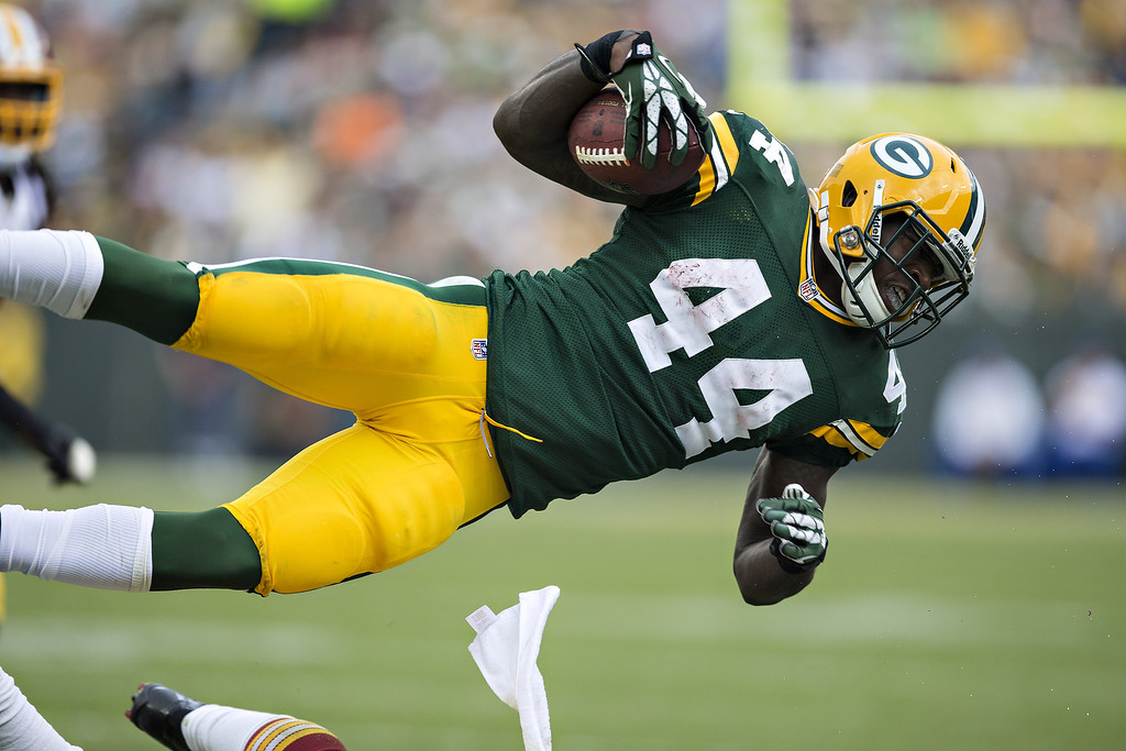 . James Starks #44 of the Green Bay Packers sails through the air on a tackle by the Washington Redskins at Lambeau Field on September 15, 2013 in Green Bay, Wisconsin. The Packers defeated the Redskins 38-20. (Photo by Wesley Hitt/Getty Images)
