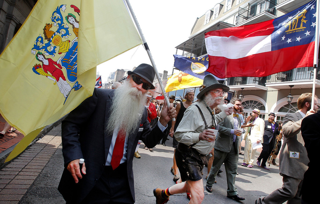 . Chris Porrovecchio of Kendall Park, New Jersey ,left, carries the New Jersey state flag during a parade through the French Quarter kicking off the fourth annual Just For Men National Beard and Moustache Championships Saturday, September 7, 2013 in New Orleans. Contestants competed in 18 different categories including Dali, full beard natural and sideburns.  (AP Photo/Susan Poag)