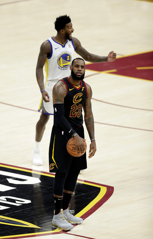 . Cleveland Cavaliers\' LeBron James holds the basketball as Golden State Warriors\' Jordan Bell reacts during the first half of Game 3 of basketball\'s NBA Finals, Wednesday, June 6, 2018, in Cleveland. (AP Photo/Tony Dejak)