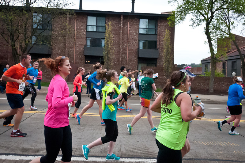 Megan looking strong at the 5 mile mark. Green shirt and orange tie-dyed shorts. Just right of center. Almost missed her!