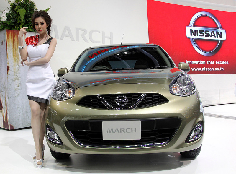 . A modes poses next to a face-lifted Nissan March subcompact, also called Nissan Micra, on the press day of the Bangkok Motor Show in Bangkok, Thailand, Tuesday, March 26, 2013. The 34th running of the auto show is opened to the public from Wednesday. (AP Photo/Sakchai Lalit)