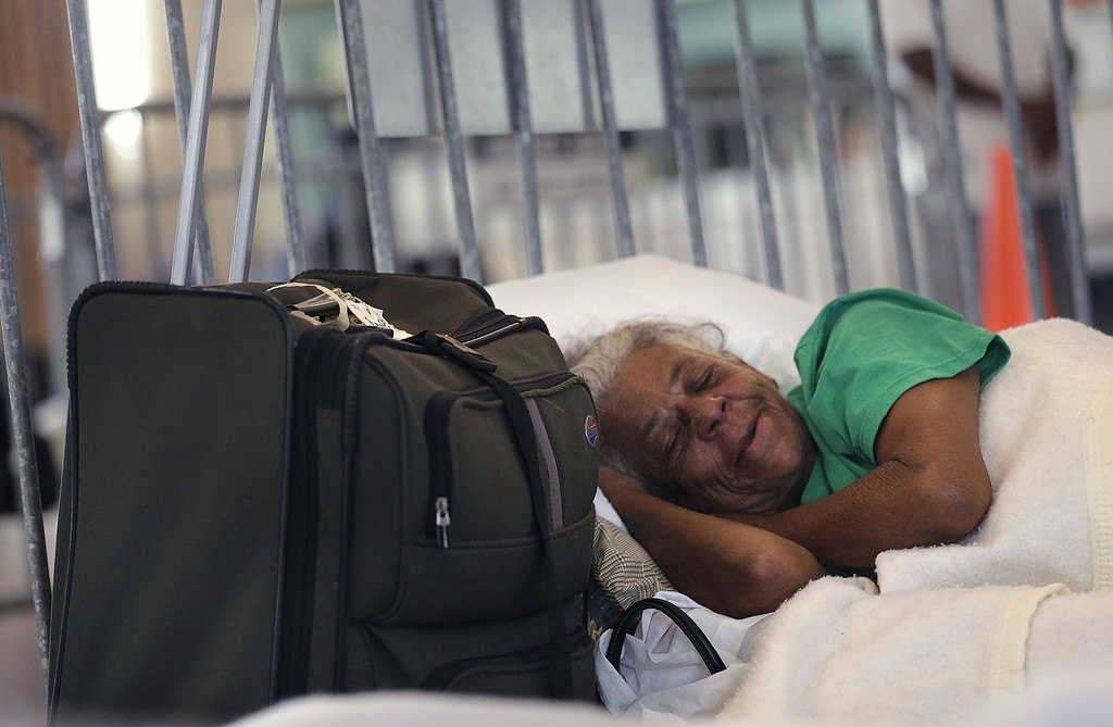 . Davina Bartholemew rests in a cot at an evacuation shelter in Belle Chasse, La., in anticipation of Tropical Storm Karen, Saturday, Oct. 5, 2013. The East Bank of Plaquemines Parish has been under a mandatory evacuation, which has been downgraded to a voluntary evacuation. (AP Photo/Gerald Herbert)