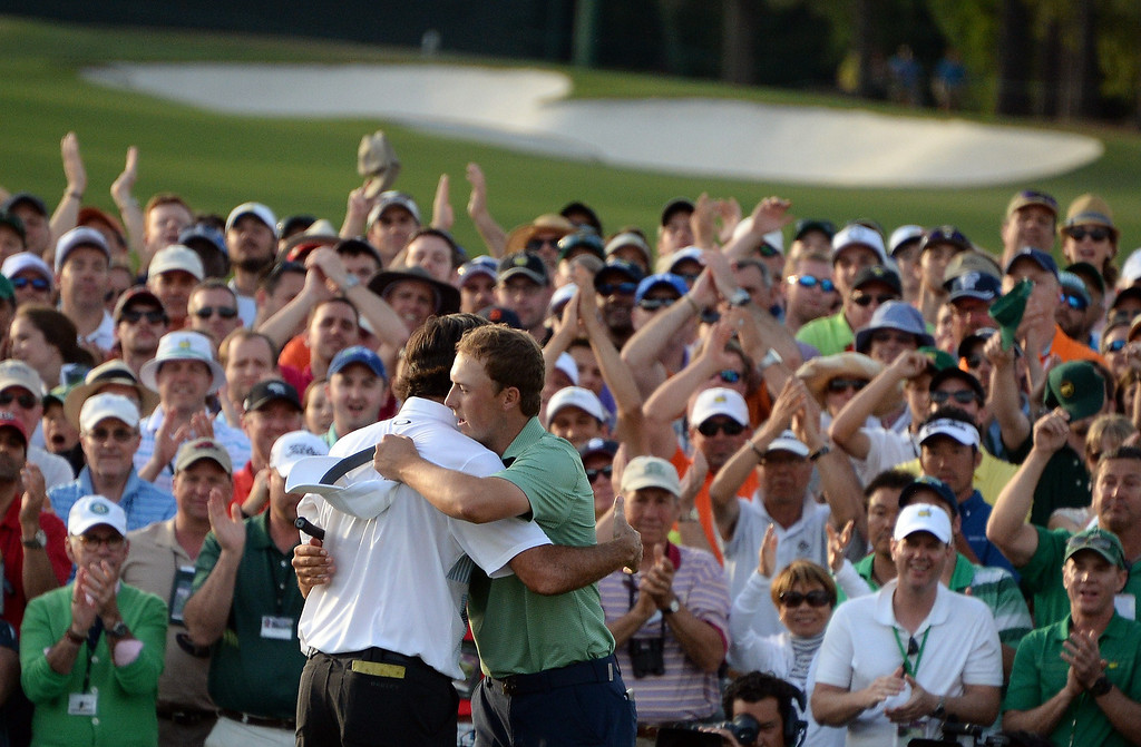 . Bubba Watson of the US embraces Jordan Spieth after putting on the 18th green during the 78th Masters Golf Tournament at Augusta National Golf Club on April 13, 2014 in Augusta, Georgia. Watson won his second Masters finishing 8-under par.    JIM WATSON/AFP/Getty Images