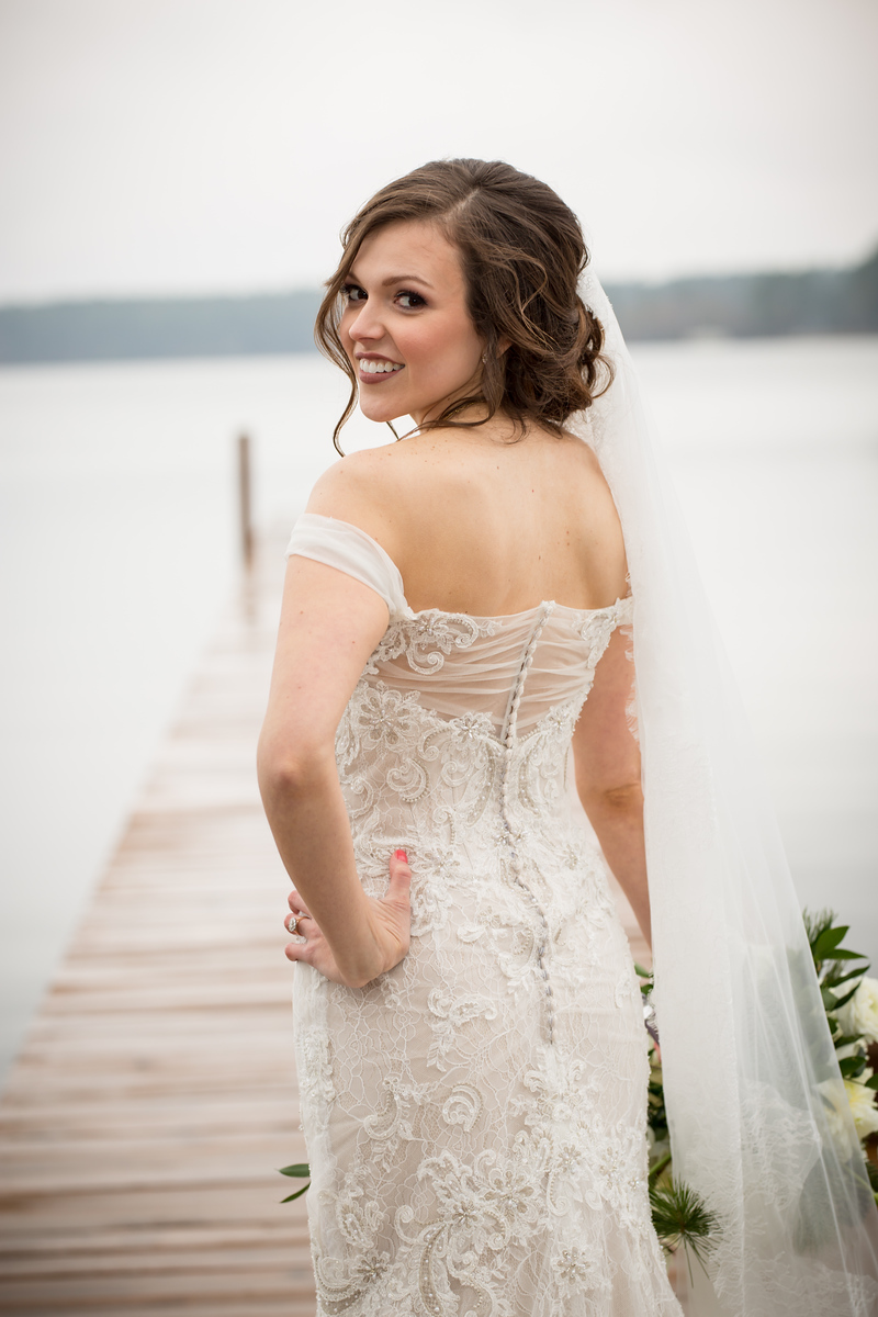 A bride standing on a doc of showing off her lace wedding dress