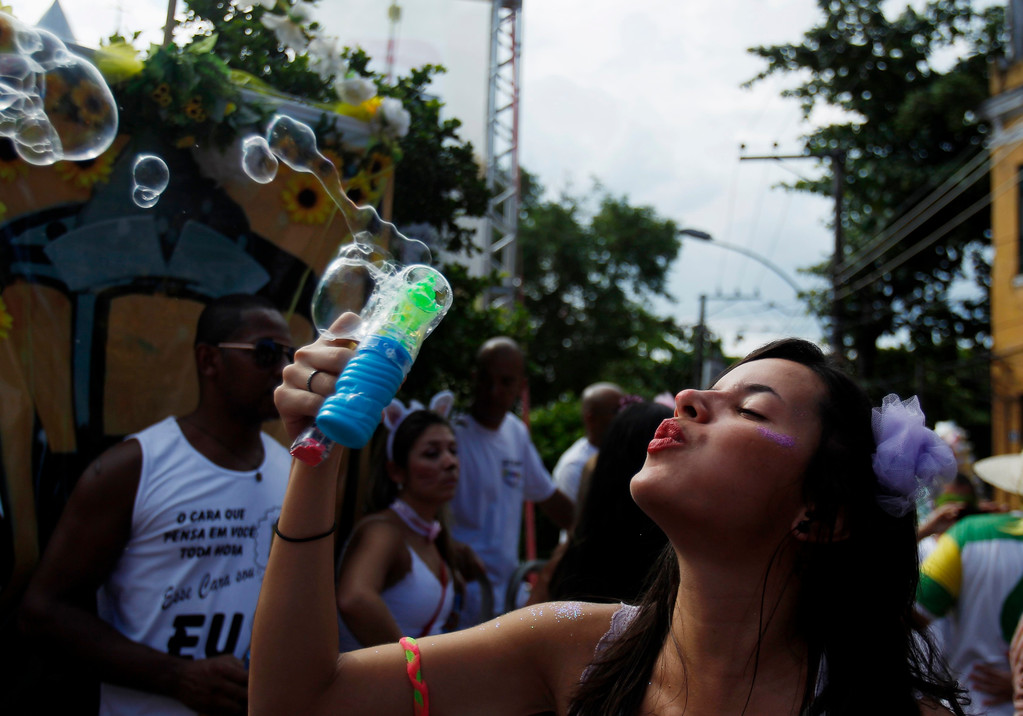 ". A reveller blows bubbles during the annual block party known as the ""Ceu na Terra\"" (or Sky on Earth), one of the many carnival parties to take place in the neighborhoods of Rio de Janeiro February 2, 2013. REUTERS/Pilar Olivares"