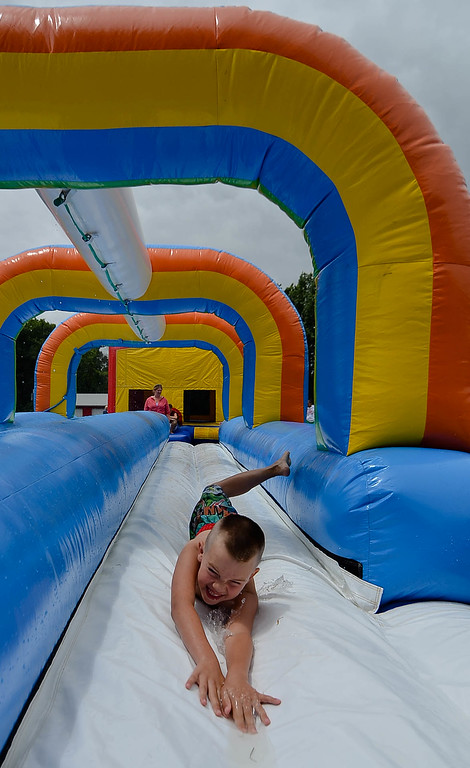 . Eric Bonzar/EBonzar@morningjournal.com<p> Bruce Wilk, 7, zips down a water slide at Camp I.D.E.A.S. carnival July 16.