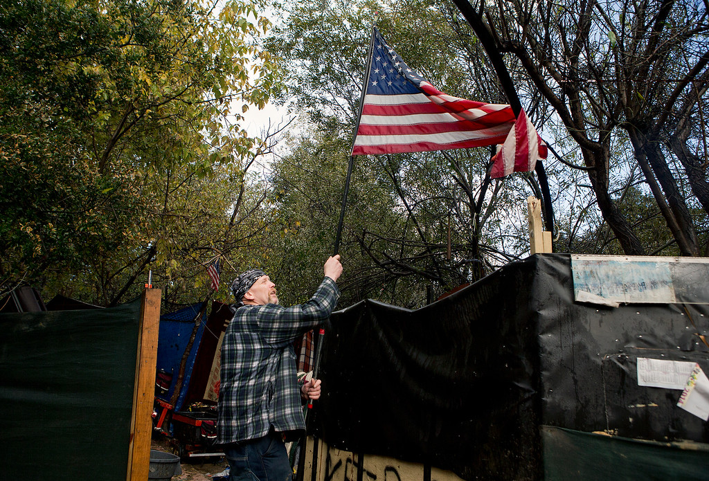 . Troy (no last name given) removes the flag from his campsite as he finishes packing in the homeless encampment known as The Jungle in San Jose, Calif., on Wednesday, Dec. 3, 2014. (LiPo Ching/Bay Area News Group)