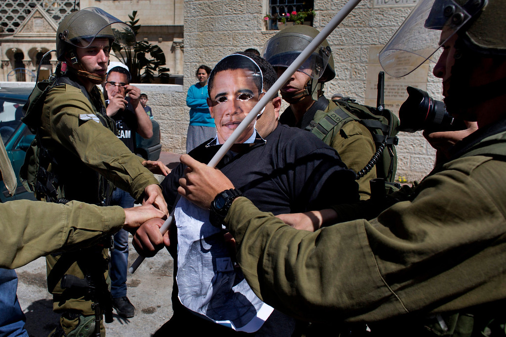 . Israeli soldiers scuffle with a Palestinian activist wearing a mask of U.S. President Barack Obama during a protest in the West Bank town of Hebron, Wednesday, March 20, 2013. (AP Photo/Bernat Armangue)