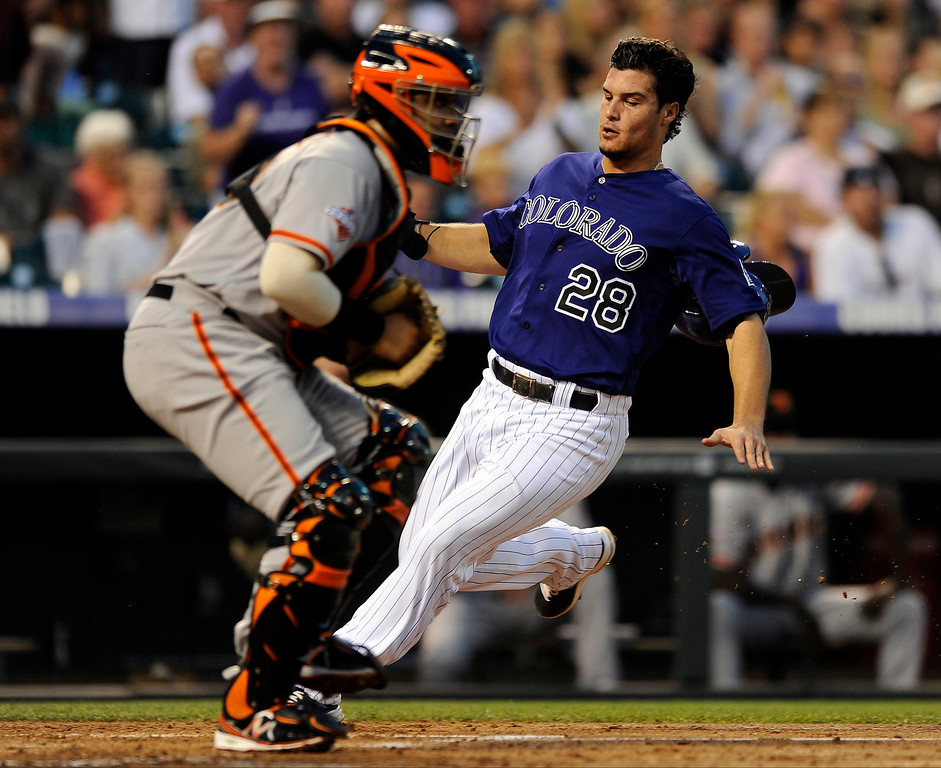 . Colorado Rockies\' Nolan Arenado beats the throw to San Francisco Giants catcher Hector Sanchez at home plate to score during the third inning of a baseball game on Tuesday, Aug. 27, 2013, in Denver. Arenado scored on a Charlie Blackmon RBI double. (AP Photo/Jack Dempsey)