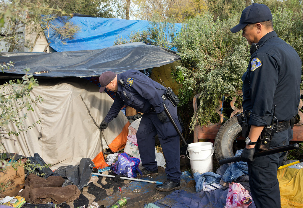 . San Jose Police Department officers check a campsite for any remaining people living in the homeless encampment known as The Jungle in San Jose, Calif., on Thursday, Dec. 4, 2014. (LiPo Ching/Bay Area News Group)