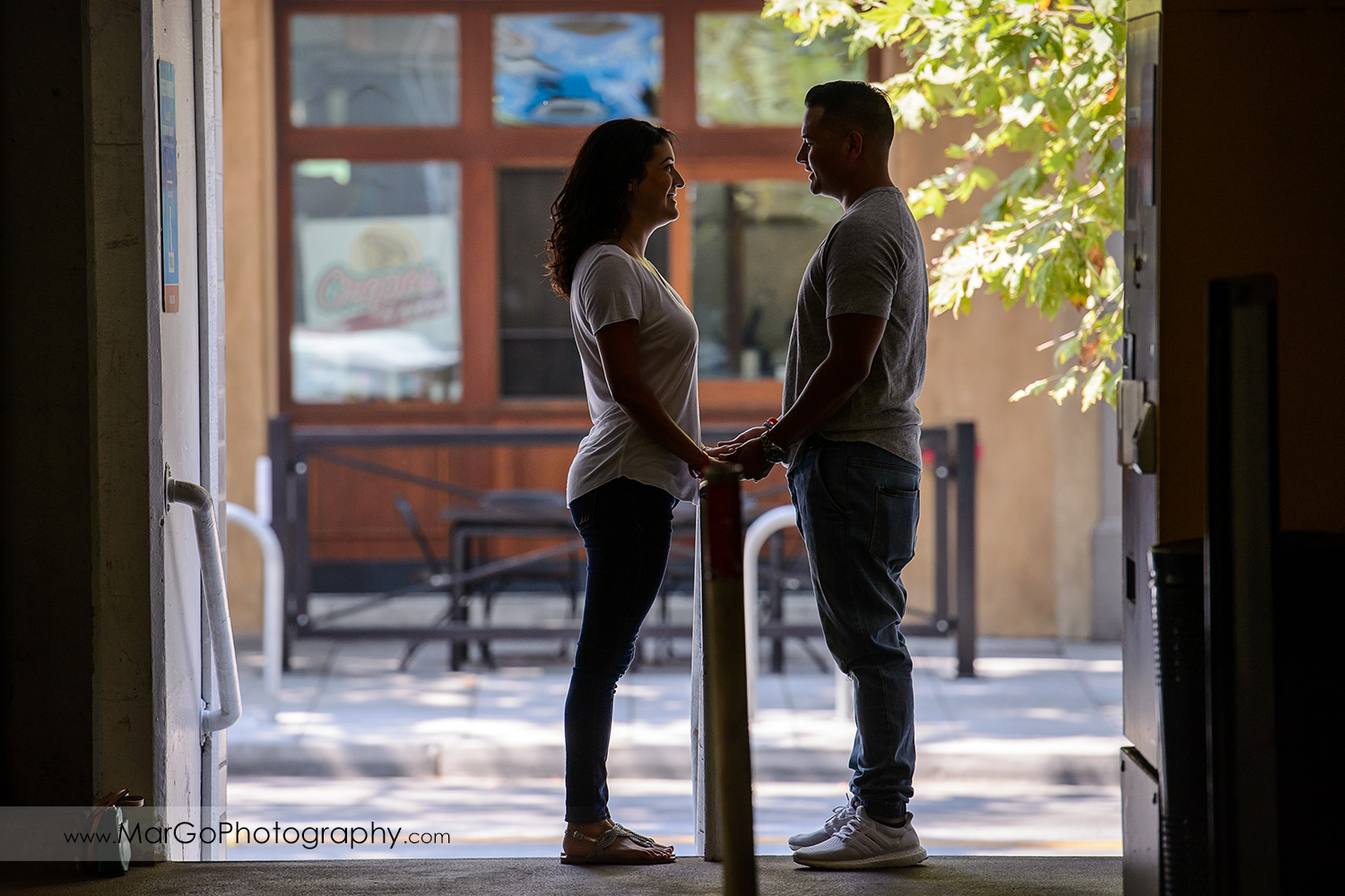 couple facing each other and holding hands during engagement session in entrance to San Pedro Square Market garage in San Jose