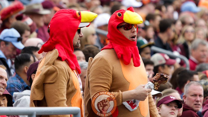 A pair of fans dressed as turkeys hold a turkey leg in the East Stands. (Mark Umansky/TheKeyPlay.com)