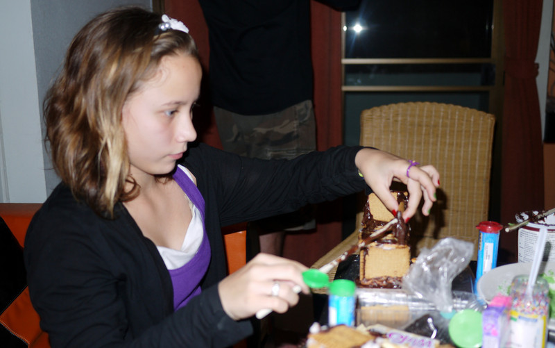 Ana concentrates on applying the nutella to her gingerbread house creation