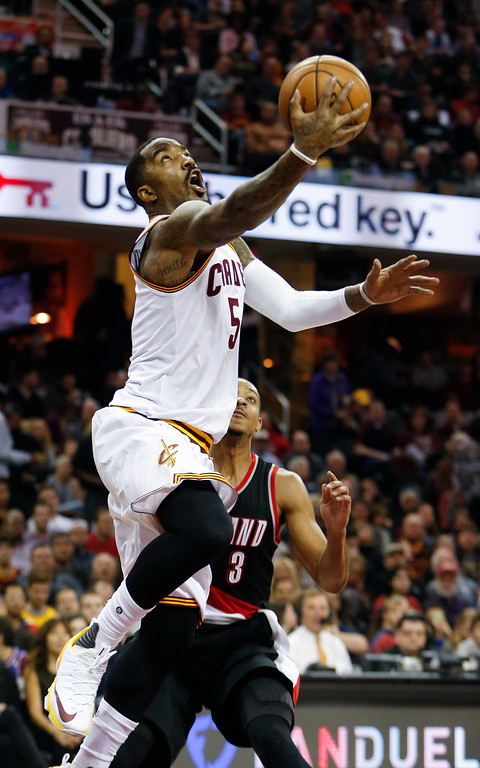 . Cleveland Cavaliers\' J.R. Smith (5) scores past Portland Trail Blazers\' C.J. McCollum (3) during the first half of an NBA basketball game, Wednesday, Nov. 23, 2016, in Cleveland. (AP Photo/Ron Schwane)