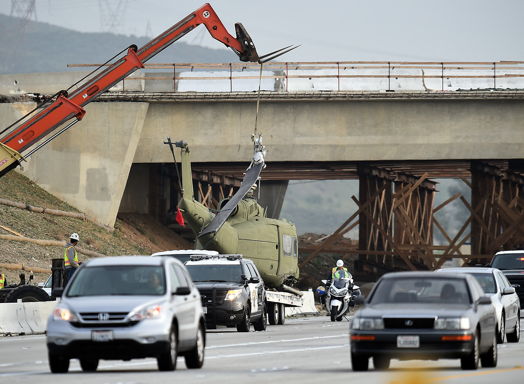 . Cars drive by as crews remove a movie prop military helicopter from the southbound lanes of the 15 freeway near Summit Ave in Fontana, CA, Friday, February 20, 2015. The copter fell off a flat bed trailer after hitting an over cross. (Jennifer Cappuccio Maher/Inland Valley Daily Bulletin)