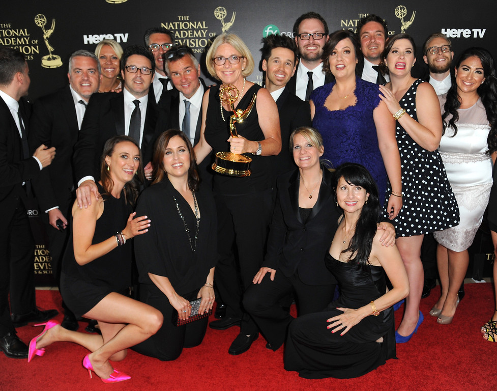 ". Mary Connelly, center, and the crew of ""The Ellen DeGeneres Show\"" pose in the press room with the award for outstanding talk show entertainment at the 41st annual Daytime Emmy Awards at the Beverly Hilton Hotel on Sunday, June 22, 2014, in Beverly Hills, Calif. (Photo by Richard Shotwell/Invision/AP)"