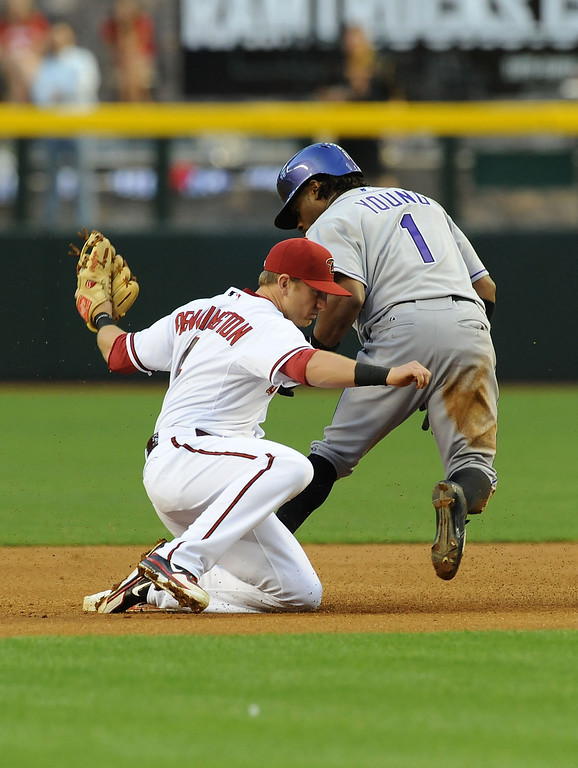 . PHOENIX, AZ - APRIL 25:  Cliff Pennington #4 of the Arizona Diamondbacks tags out Eric Young Jr #1 of the Colorado Rockies at second base at Chase Field on April 25, 2013 in Phoenix, Arizona.  (Photo by Norm Hall/Getty Images)