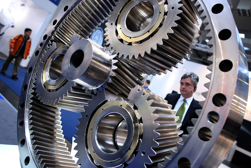 Description of . A visitor looks at a gear wheel at NKE Bearings booth at the industrial trade fair in Hanover, central Germany on April 8, 2013. The fair running from April 8 to 12, 2013 presents a cross section of key industrial technologies.  RONNY HARTMANN/AFP/Getty Images