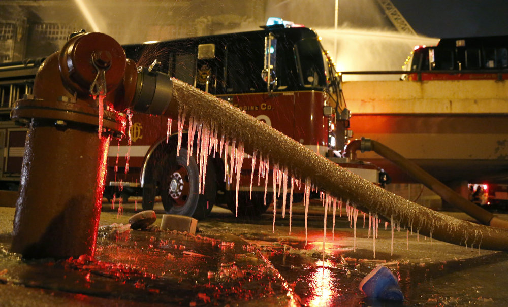 Description of . Icicles form on a fire hose from single digit temperatures as Chicago firefighters battle a five-alarm blaze in a warehouse on the city's South Side, Bridgeport neighborhood Wednesday, Jan. 23, 2013, in Chicago. (AP Photo/Charles Rex Arbogast)