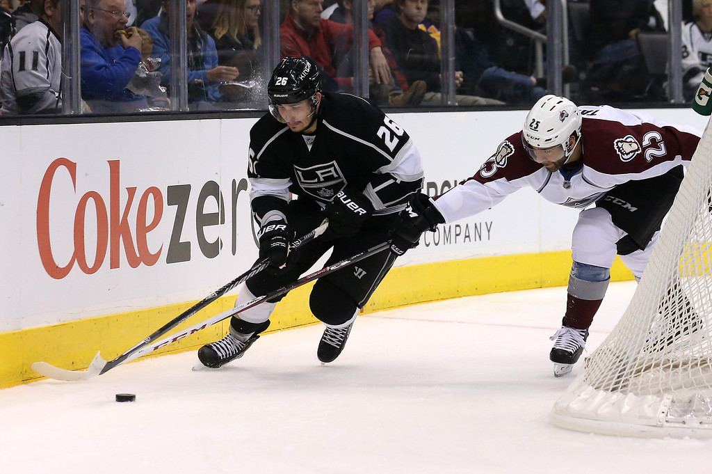 . LOS ANGELES, CA - DECEMBER 21:  Slava Voynov #26 of the Los Angeles Kings fights for the puck with Maxime Talbot #25 of the Colorado Avalanche at Staples Center on December 21, 2013 in Los Angeles, California.  (Photo by Stephen Dunn/Getty Images)