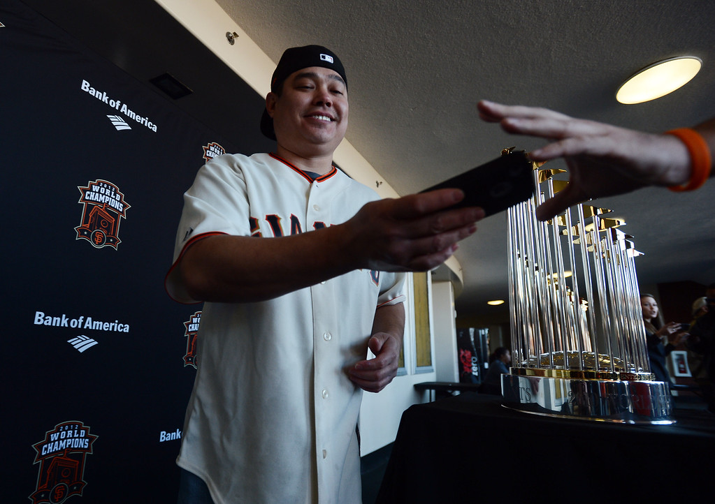 . Craig Takehara, of Sacramento, gets his camera back after being photographed with the World Series Trophy as it makes a stop at the Richmond Memorial Auditorium in Richmond, Calif. on Monday, Jan. 14, 2013.  (Kristopher Skinner/Staff)