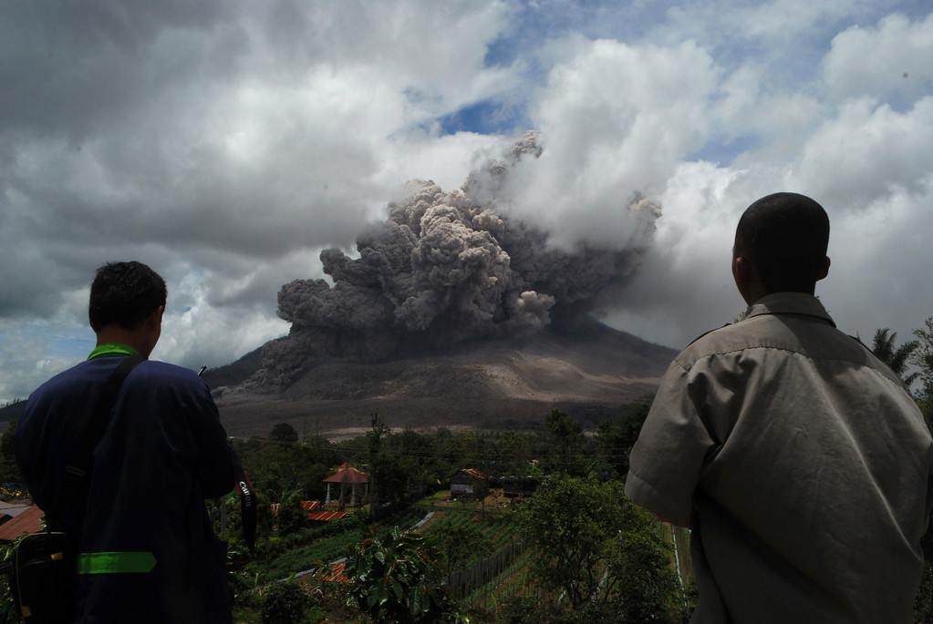 . Residents watch as dark giant ash clouds rise from the crater of Mount Sinabung volcano during an eruption on October 8, 2014, as seen from Karo district located on Indonesia\'s Sumatra island, following an earlier eruption on October 5, 2014. According to authorities hundreds of residents are still housed at evacuation centers as authorities maintains off limit danger zone around Mount Sinabung located in Indonesia\'s Sumatra island following deadly eruption in early February that killed about 17 people.  AFP PHOTO / SUTANTA  ADITYA/AFP/Getty Images