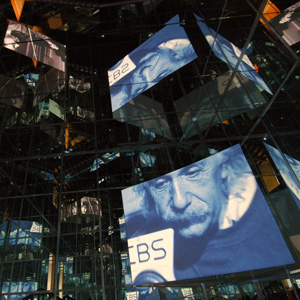 Photograph of hall of mirrors with multiple reflections of movie images of Albert Einstein on hanging screens: entrance to Einstein exhibition at Historisches Museum, Bern, 2006.