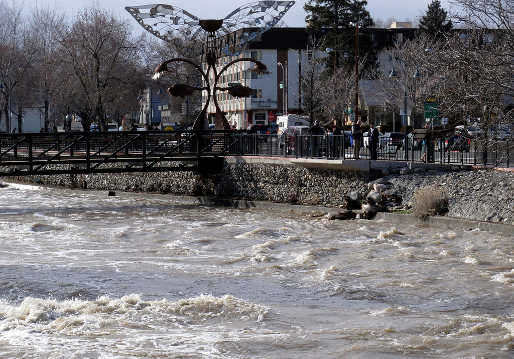 . People gather along the Truckee River in downtown Reno, Nev., Monday, Jan. 9, 2017, after floodwaters crested earlier in the day. Most bridges that had closed were reopened. (AP Photo/Scott Sonner).