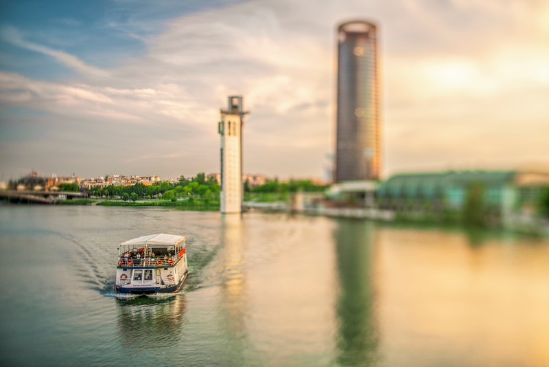 Guadalquivir River Boat Cruise In Seville, Spain. Schlinder and Sevilla Towers on the background. Selective focus through a tilted lens.