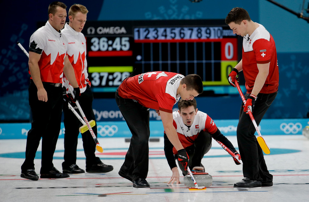 . Switzerland\'s skip Peter de Cruz, center right, throws a stone as he watches his team sweep the ice during a men\'s curling match against Canada at the 2018 Winter Olympics in Gangneung, South Korea, Sunday, Feb. 18, 2018. (AP Photo/Natacha Pisarenko)