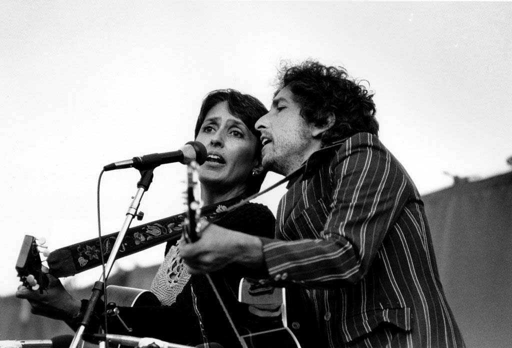 ". Folk singers Joan Baez, left, and Bob Dylan entertain over 80,000 people gathered at the Rose Bowl in Pasadena, Ca. on Sunday afternoon, June 6, 1982. The event, a nuclear disarmament rally titled ""Peace Sunday,\"" featured music, speeches and prayers. The rally is held just one day before the United Nations starts its special session on disarmament in New York. (AP Photo/Lennox McLendon)"