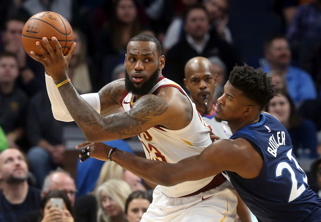. Cleveland Cavaliers\' LeBron James, left, looks for help as Minnesota Timberwolves\' Andrew Wiggins defends in the first half of an NBA basketball game Monday, Jan. 8, 2018, in Minneapolis. (AP Photo/Jim Mone)