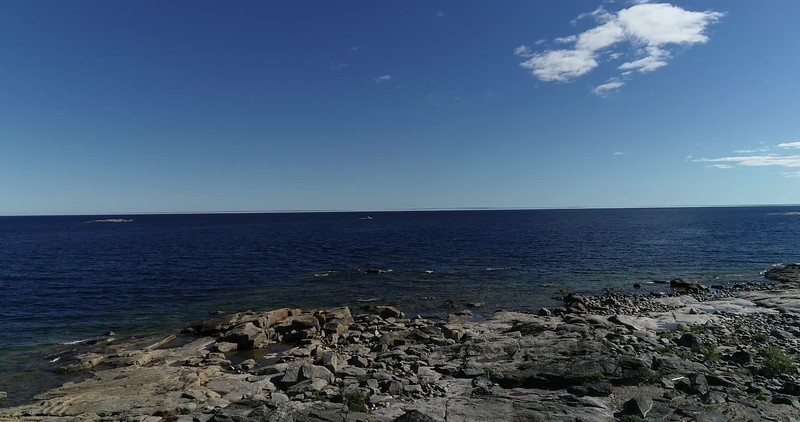 Aerial: flying over a rocky coast towards the Baltic Sea on a sunny summer day