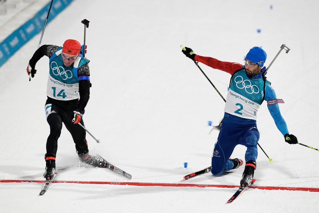. Simon Schempp, of Germany, left, and Martin Fourcade, of France, right, race across the finish line during the men\'s 15-kilometer mass start biathlon at the 2018 Winter Olympics in Pyeongchang, South Korea, Sunday, Feb. 18, 2018. (AP Photo/Andrew Medichini)