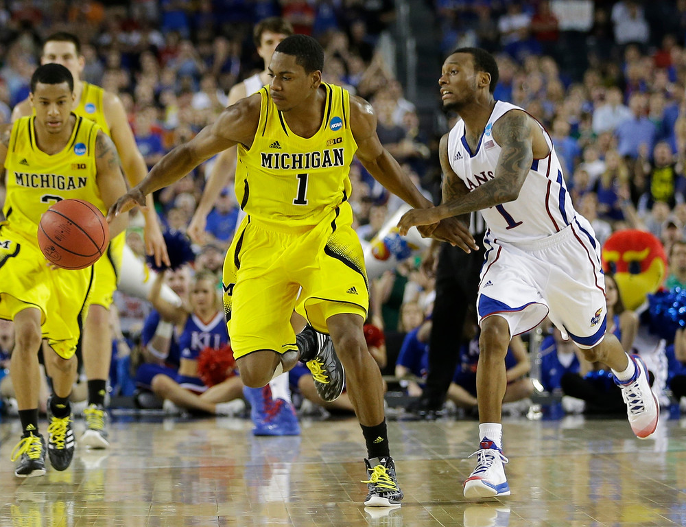 . Michigan\'s Glenn Robinson III steals the ball from Kansas\' Naadir Tharpe during overtime of a regional semifinal game in the NCAA college basketball tournament, Friday, March 29, 2013, in Arlington, Texas. (AP Photo/David J. Phillip)